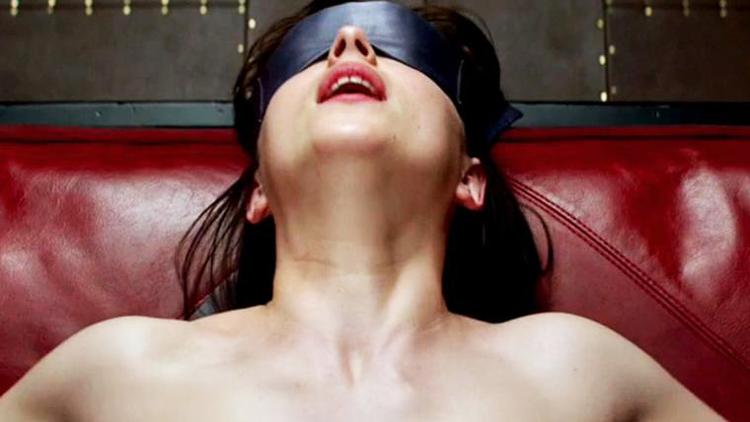 femme nue jouit les yeux bandés avec un ruban noir sur un canapé en cuir rouge