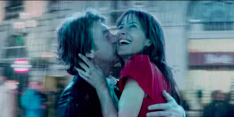 Sophie Marceau souriante dans les bras de Daniel Auteuil sous la pluie