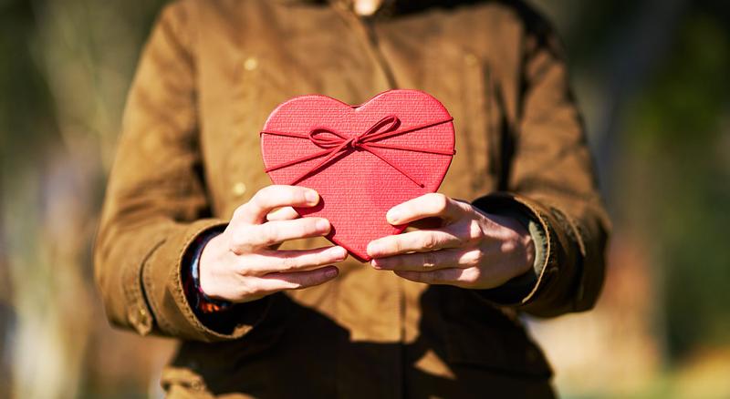 les mains d'une personne qui offre un cadeau en forme de coeur