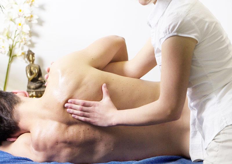 homme allongé sur le côté se fait masser le dos