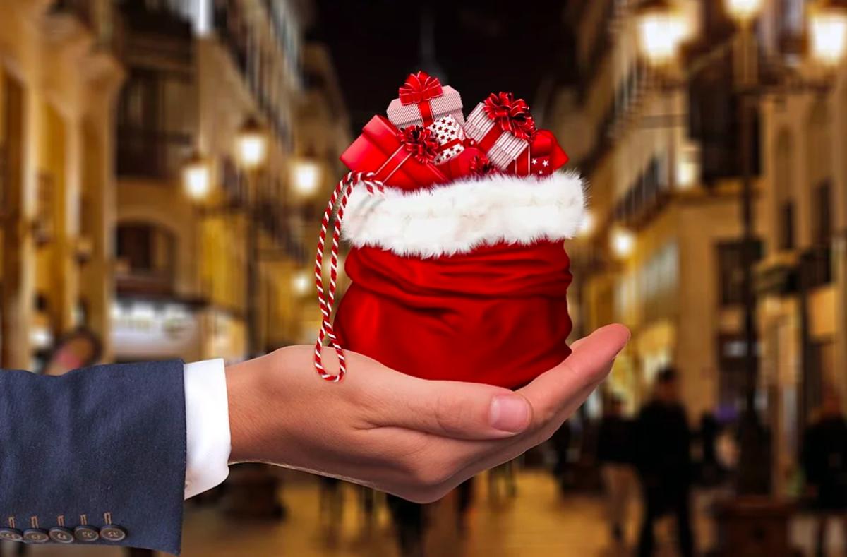 bras d'un homme en costume tend un petit cadeau de noel dans le creux de sa main