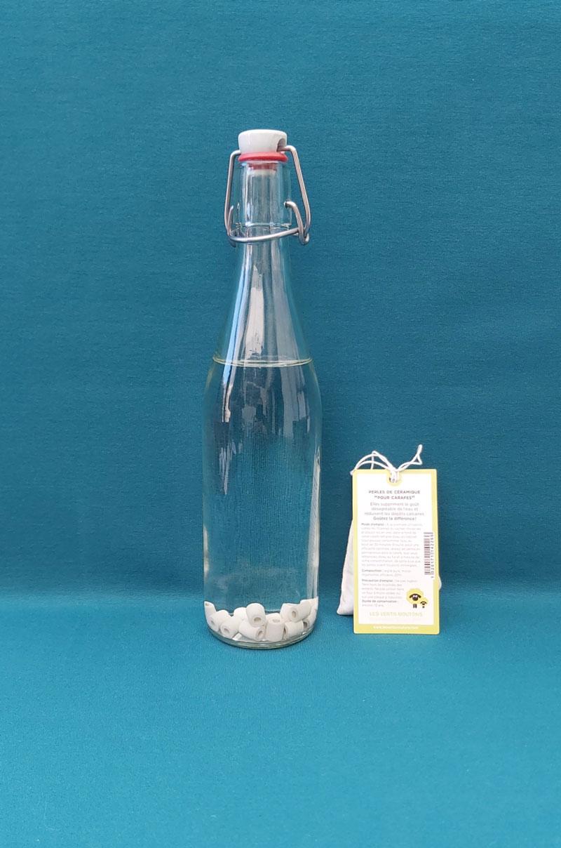 perles de céramique dans bouteille d'eau en verre sur fond bleu