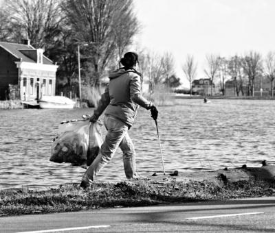 une femme marche avec des sacs de déchets qu'elle a ramassé