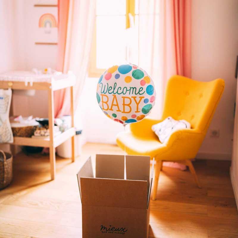 ballon avec welcome baby sortant d'un carton dans une chambre de bébé
