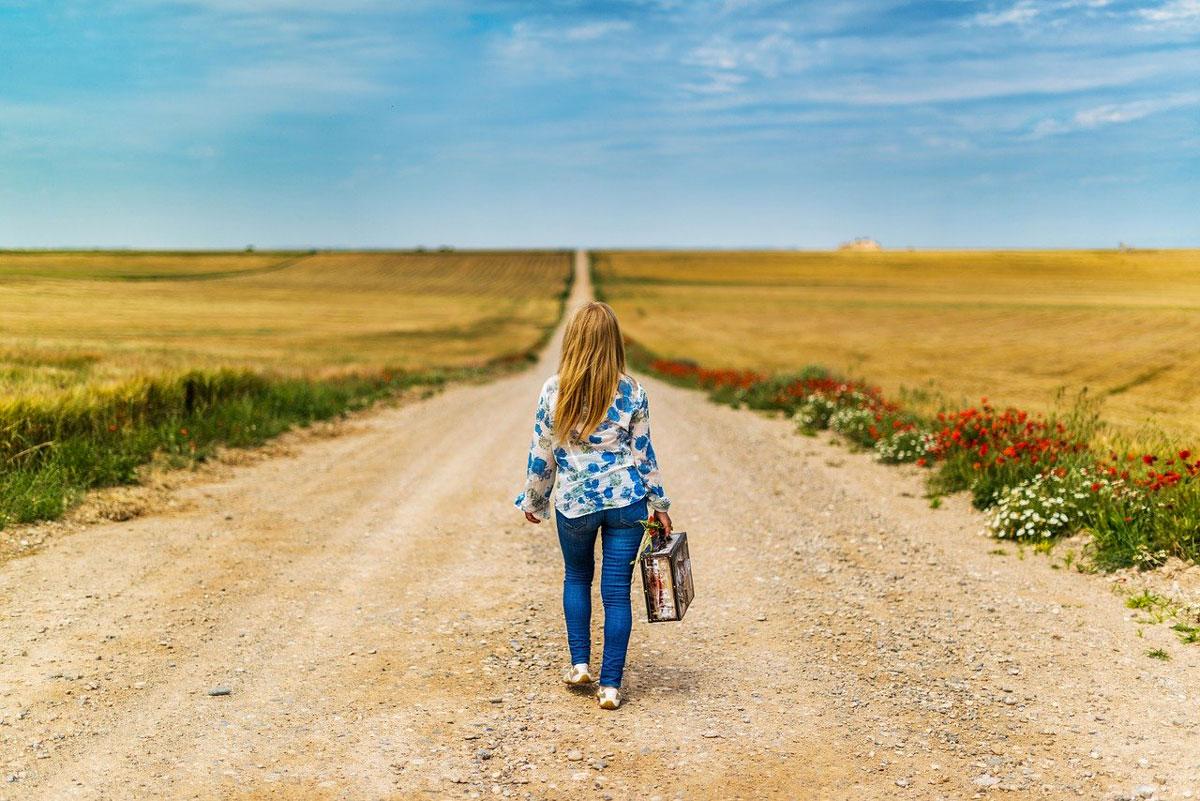 femme seule marche au milieu d'une route avec sa valise